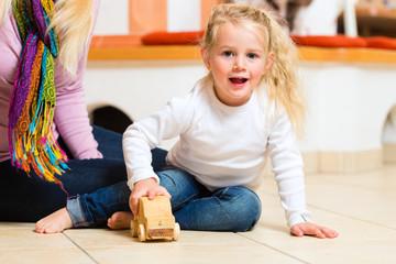 Mädchen spielt mit Holzspielzeug Auto