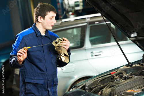 car mechanic examining oil at motor engine