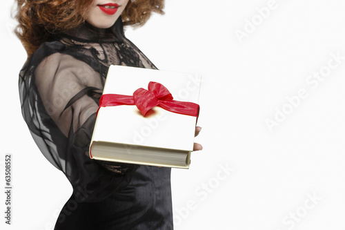 Glamorous woman holding book with big bow