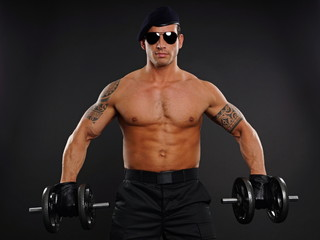 Portrait of muscular soldier at sunglasses holding dumbbells