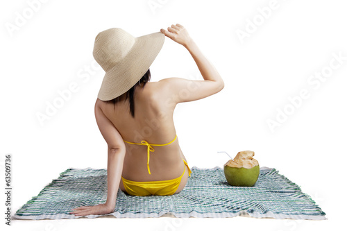 Woman in bikini sitting on mat isolated