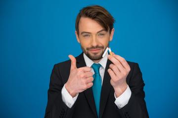 handsome businessman holding broken cigarette