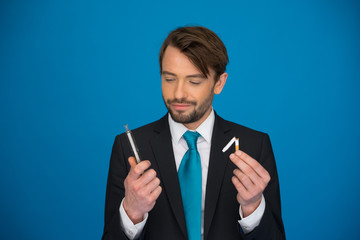handsome businessman holding broken cigarette