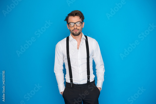 handsome man on blue wearing white shirt and braces