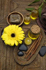 massage oil and with yellow gerbera on burlap texture
