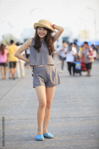 young and pretty asian woman wearing straw hat standing and post