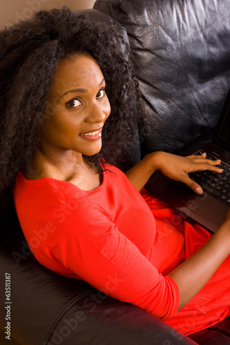 young african american woman at home with a computer.