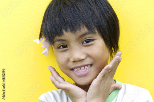 Portrait of cute little girl on yellow background close-up