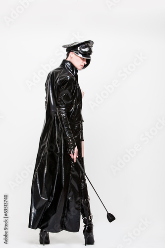 Domina woman with hat, whip and raincoat
