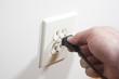 Leinwanddruck Bild - A hand putting a two prong plug into a wall socket.