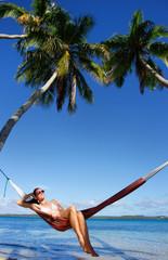 Young woman in bikini sitting in a hammock between palm trees, O