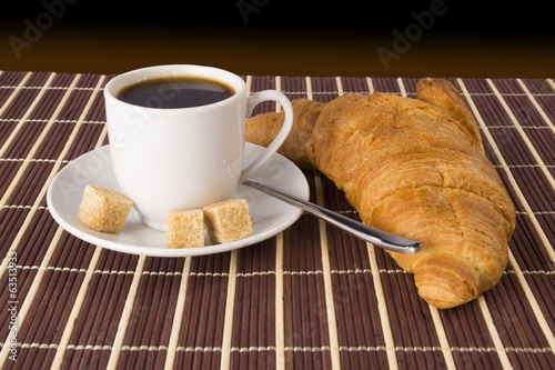 Cup of coffee and a croissant on the mat