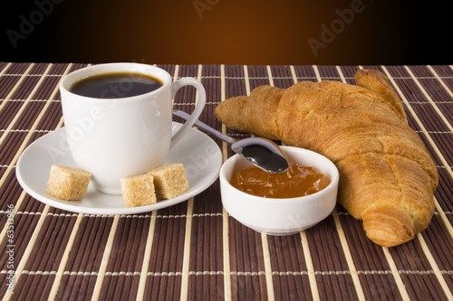 Cup of coffee and a croissant and jam