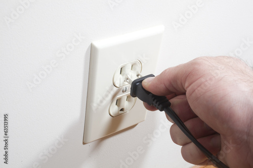 A hand putting a two prong plug into a wall socket. - 63513995