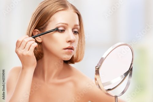 beautiful woman doing  makeup with brush in the mirror