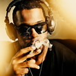cool african man smoking joint wearing headphones - 63514755