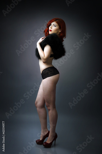 Curvy woman posing in lingerie, full length studio portrait