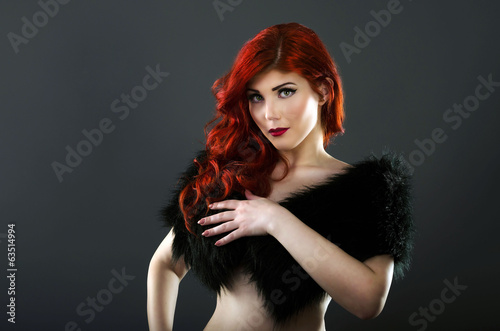 Topless redhead woman covering her breasts with a black fur coat