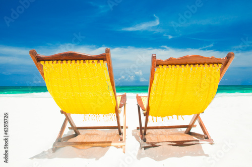 two yellow beach chairs and umbrella on sand beach. Holidays