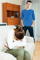Crying young woman against standing man