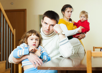 Young couple with children after quarrel at home