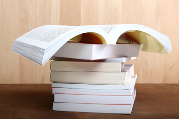 A stack of books on a wooden table.