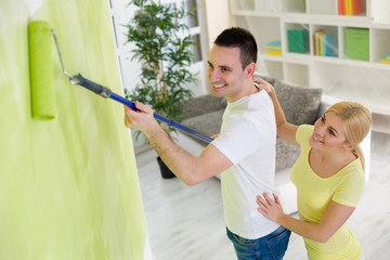 Smiling couple painting hew home