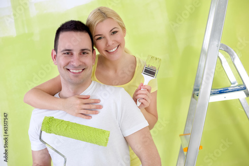 Young happy handy couple painting new house