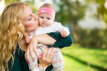 Mother kiss baby in  hands