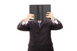 Businessman holding a book in front of his face