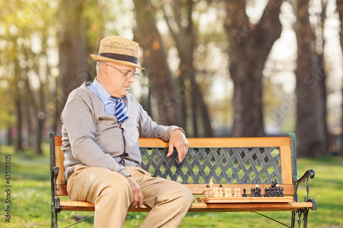 Lonley senior playing chess outdoors