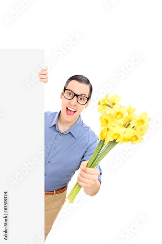 Man holding flowers behind a blank panel