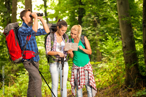 group of hikers with map and binoculars