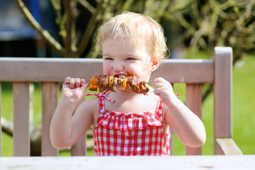 Funny toddler girl eating tasty grilled meat outdoors