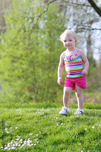 Cute toddler girl playing in summer park