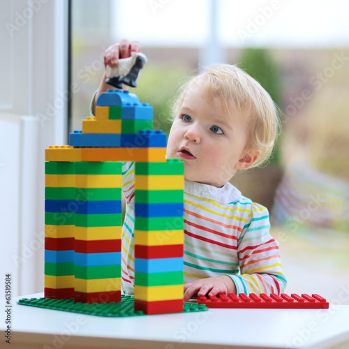 Happy child cute toddler girl building house from plastic blocks