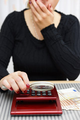 woman watching sum on calculator with magnifying glass and cant