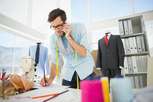 Fashion designer working on his designs while on call
