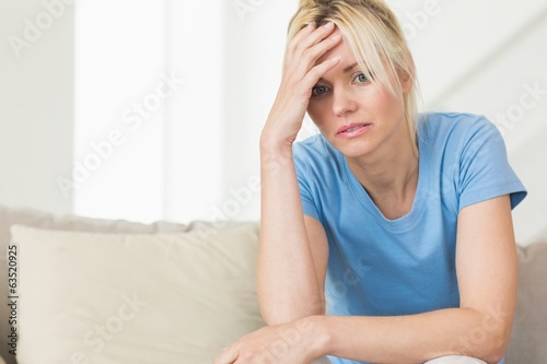 Worried young woman sitting in living room