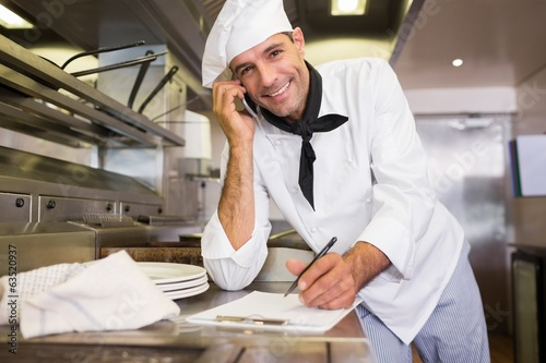 Male cook writing on clipboard while using cellphone in kitchen