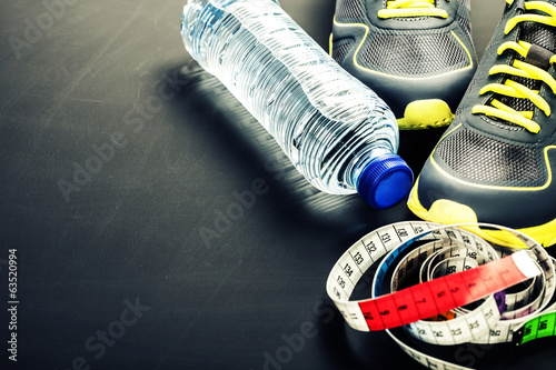 Sport shoes, measuring tape and water