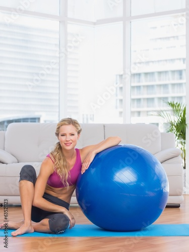 Slim blonde sitting beside exercise ball smiling at camera