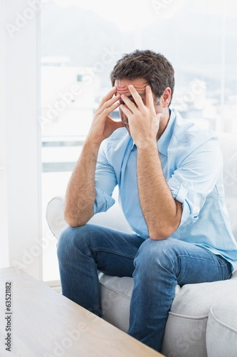Man with headache sitting on the couch