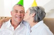 Senior couple sitting on couch wearing party hats