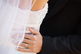 Mid section of newlywed couple embracing