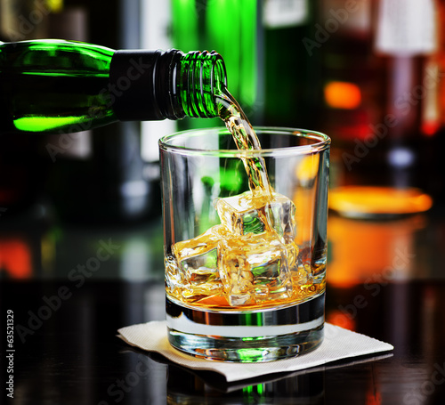 Whiskey pouring a glass in a bar