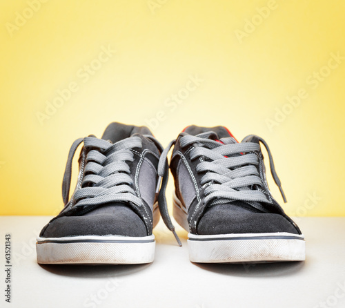 Pair of grey sneakers on colorful background