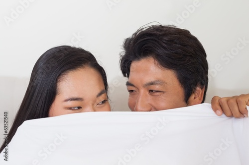 Happy couple holding duvet over face