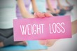 Woman holding pink card saying weight loss