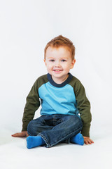 Redhead little boy sitting on the floor and smiling